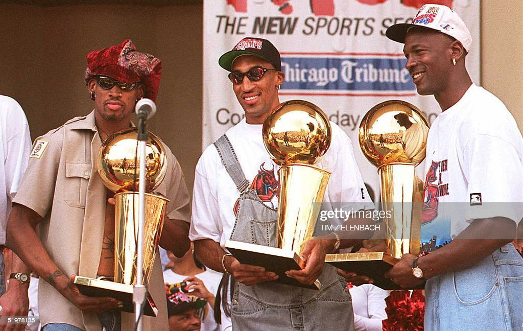 Chicago Bulls players Dennis Rodman (L), Scottie Pippen (C) and Michael Jordan (R) hold three of the team's four recent Larry O'Brien trophies 18 June at a rally for the team in Grant Park in Chicago. Thousands of fans crowded into the park to see the NBA champions.