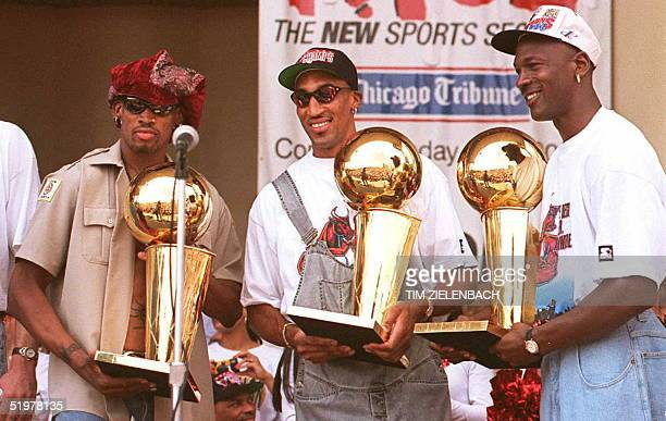 Chicago Bulls players Dennis Rodman Scottie Pippen and Michael Jordan hold three of the team's four recent Larry O'Brien trophies 18 June at a rally...