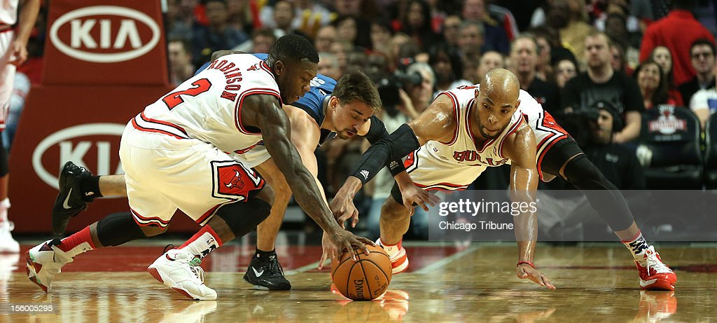 Chicago Bulls point guard Nate Robinson (2) and power forward Taj Gibson (right) fight for a loose ball with Minnesota Timberwolves point guard Alexey Shved (1) in the first half at the United Center in Chicago, Illinois, on Saturday, November 10, 2012.