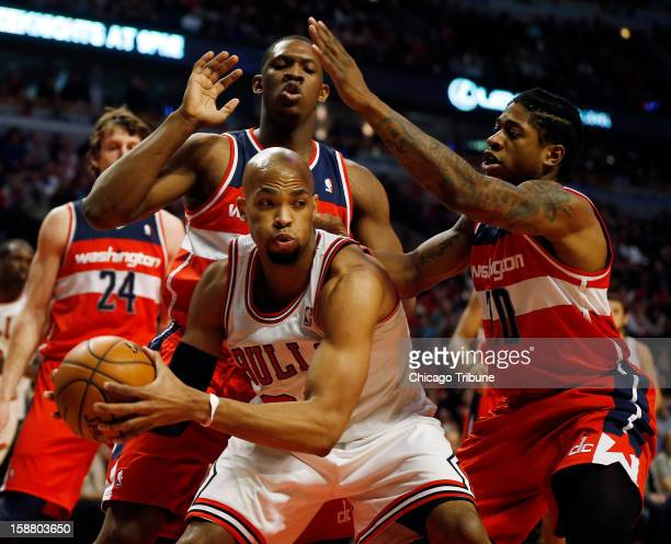 Chicago Bulls power forward Taj Gibson is defended by Washington Wizards power forward Kevin Seraphin and Cartier Martin during game action at the...