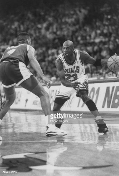 Chicago Bulls' star Michael Jordan furiously dribbling ball around opponent in NBA championship basketball game between the Bulls the LA Lakers at...