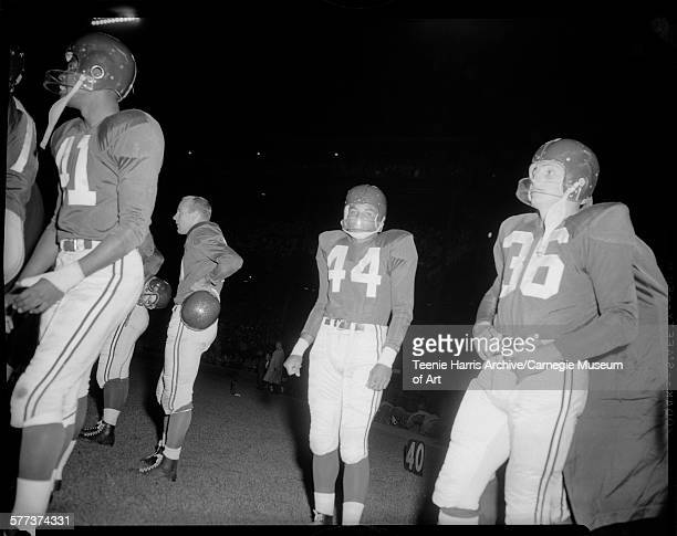 Chicago Cardinals football players including no 44 Ollie Matson standing on Forbes Field during game against the Pittsburgh Steelers at night...