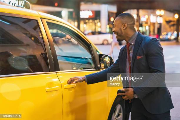 chicago city smiling businessman getting on yello cab downtown taxi - mlenny stock pictures, royalty-free photos & images