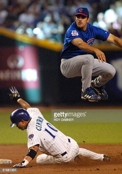 Chicago Cubs Alex Gonzalez jumps over Arizona Diamondbacks Alex Cintron to complete a double play off the bat of Chad Moeller during the second...