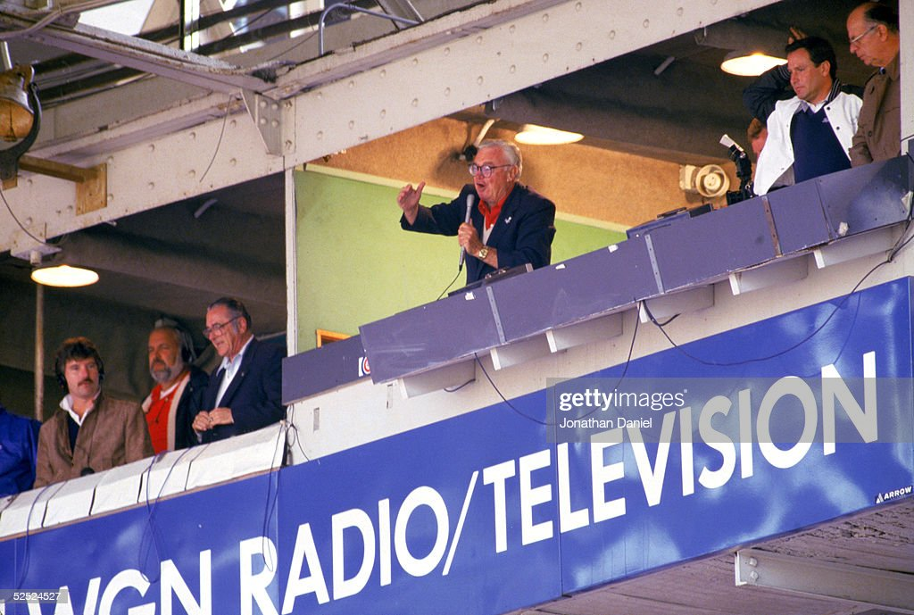 Chicago Cubs baseball announcer and Baseball Hall of Fame inductee Harry Caray conducts fans singing 'Take Me Out to the Ball Game' from his television booth during the seventh inning stretch in a regular season game in 1997 at Wrigley Field in Chicago, Illinois.