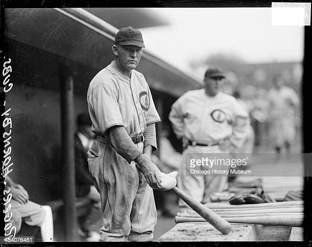 Chicago Cubs baseball player Rogers Hornsby holding a rosin bag on a baseball bat standing in a dugout at Wrigley Field Chicago Illinois 1929