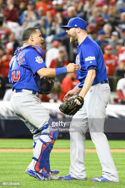 Chicago Cubs catcher Willson Contreras celebrates with relief pitcher Wade Davis following game five of the NLDS between the Chicago Cubs and the...