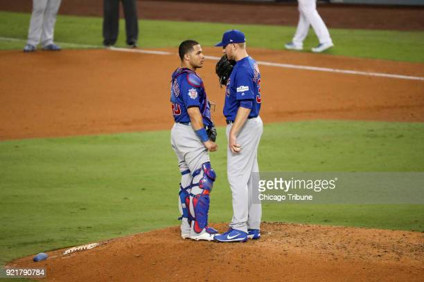 Chicago Cubs catcher Willson Contreras left talks with relief pitcher Mike Montgomery during the sixth inning against the Los Angeles Dodgers in Game...