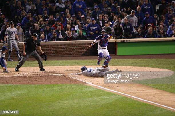 Chicago Cubs catcher Willson Contreras takes a high throw from the outfield as the Los Angeles Dodgers' Yasiel Puig slides in safely in the fourth...