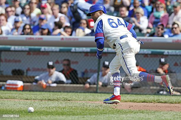 Chicago Cubs Emilio Bonifacio hits a sacrifice bunt to advance Cubs Darwin Barney in the seventh inning against the Miami Marlins at Wrigley Field in...
