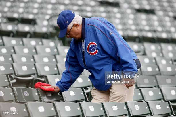 Chicago Cubs employee wipes off seats before game four of the National League Division Series between the Washington Nationals and the Chicago Cubs...