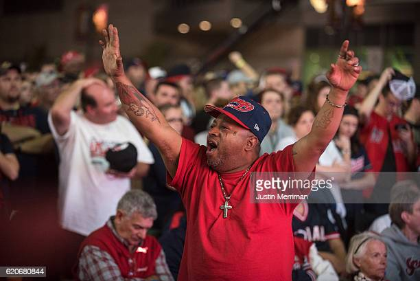 Chicago Cubs fan reacts as Cleveland Indians fans stand in the background as they watch the big screen outside of Progressive Field during game 7 of...