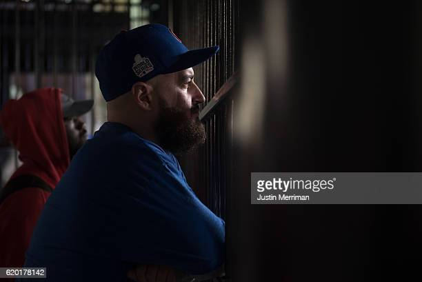 Chicago Cubs fan Stephen Caton of St Louis watches Game 6 of the World Series between the Cubs and the Cleveland Indians through a fence at...