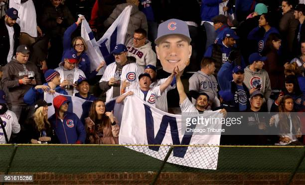 Chicago Cubs fans hold a giant cutout of center fielder Albert Almora Jr as they celebrate a 10 victory against the Milwaukee Brewers at Wrigley...