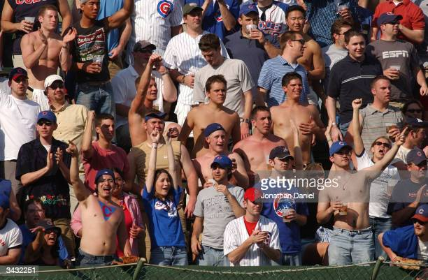 Chicago Cubs' fans in the left field bleechers, dressed for unseasonably warm April weather, cheer during a game against the Cincinnati Reds on April...