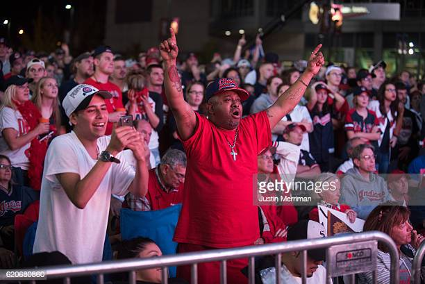 Chicago Cubs fans react as Cleveland Indians fans stand in the background as they watch the big screen outside of Progressive Field during game 7 of...
