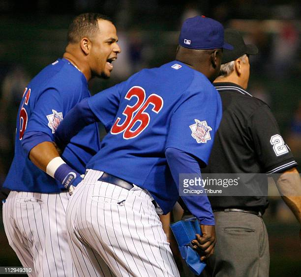 Chicago Cubs first base coach Gary Matthews restrains Aramis Ramirez while arguing with first base umpire Tom Hallion in the fourth inning against...