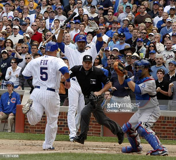 Chicago Cubs Jake Fox scores the lead run in the seventh inning on a sacrifice fly to center by teammate Kosuke Fukudome during a MLB game against...