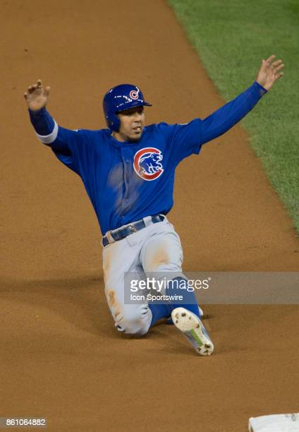 Chicago Cubs left fielder Jon Jay slides into third base on a wild pitch during game five of the NLDS between the Washington Nationals and the...