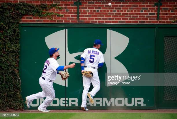 Chicago Cubs left fielder Kyle Schwarber and Chicago Cubs center fielder Albert Almora Jr are unable to catch a double by Cincinnati Reds first...