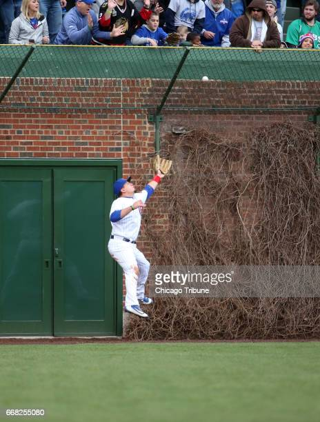 Chicago Cubs left fielder Kyle Schwarber makes a juggling catch on a hit that was ruled a double by the Los Angeles Dodgers' Enrique Hernandez in the...
