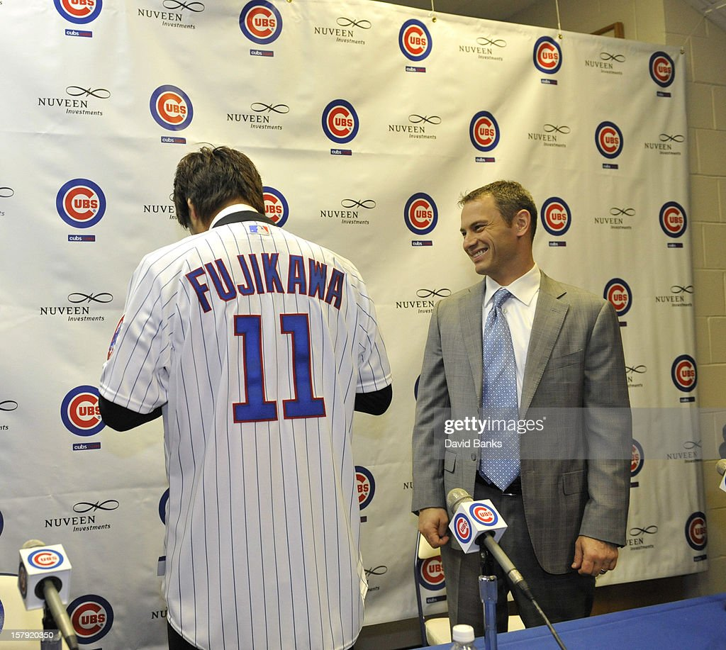 Chicago Cubs new pitcher Kyuji Fujikawa tries on his new jersey as Chicago Cubs general manager Jed Hoyer watches December 7, 2012 at Wrigley Field in Chicago, Illinois.