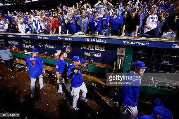 Chicago Cubs players celebrate in the dugout after defeating the Pittsburgh Pirates to win the National League Wild Card game at PNC Park on October...