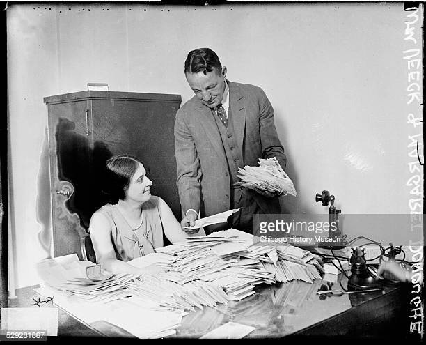 Chicago Cubs President Bill Veeck Sr holding stack of World Series ticket orders standing next to Margaret Donoughe in the Cubs business office...