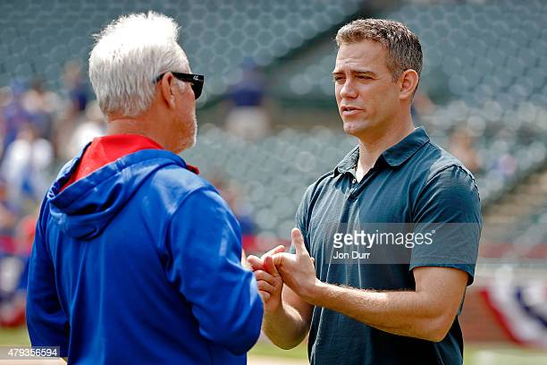 Chicago Cubs President of Baseball Operations Theo Epstein talks with manager Joe Maddon before the game against the Miami Marlins at Wrigley Field...