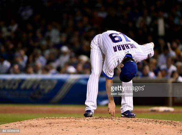 Chicago Cubs relief pitcher Koji Uehara removes debris from the mound during the game between the Pittsburgh Pirates and the Chicago Cubs on August...