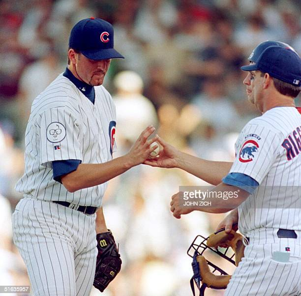 Chicago Cubs' relief pitcher Terry Adams hands the ball to manager Jim Riggleman after giving up three runs and allowing two consecutive Milwaukee...