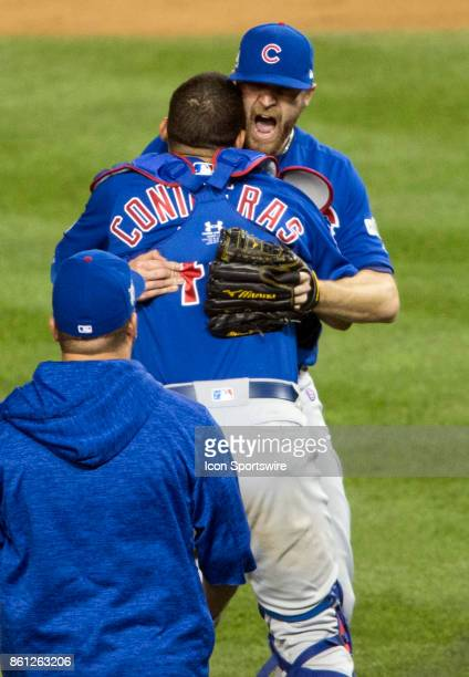 Chicago Cubs relief pitcher Wade Davis and catcher Willson Contreras celebrate the Cubs victory at the end of game five of the NLDS between the...