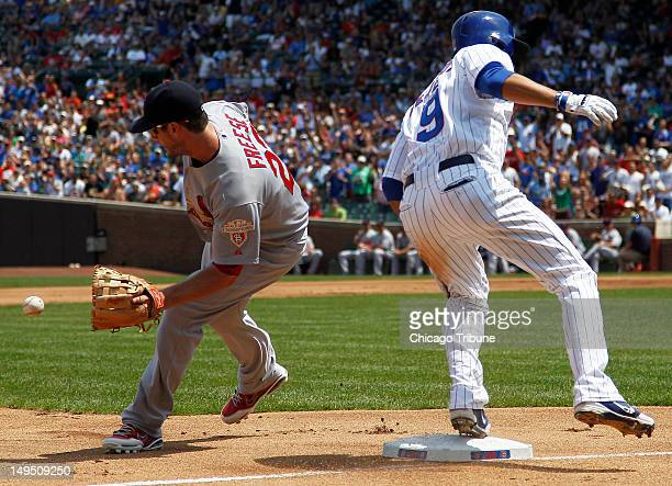 Chicago Cubs right fielder David DeJesus is safe with a triple as St Louis Cardinals third baseman David Freese receives the ball in the first inning...