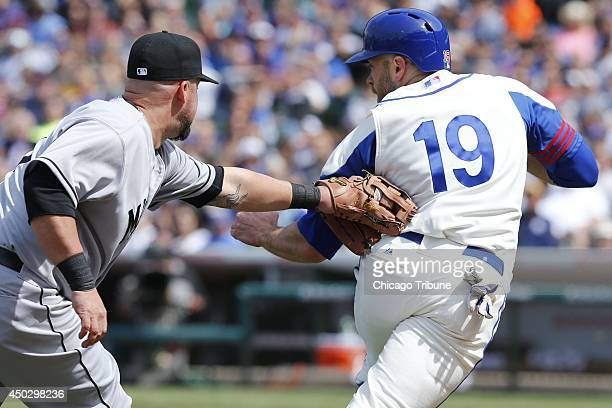 Chicago Cubs right fielder Nate Schierholtz is out as Miami Marlins third baseman Casey McGehee tags him out on a rundown between home plate and...