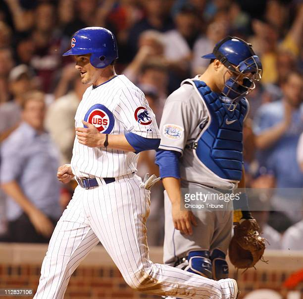 Chicago Cubs' Ryan Theriot left smiles as crosses the plate past Los Angeles Dodgers catcher Russell Martin after scoring on a single by Derrek Lee...
