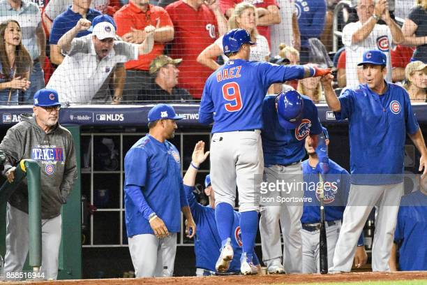 Chicago Cubs second baseman Javier Baez is congratulated by catching coach Mike Borzello in the dugout after scoring the first run of the game in the...