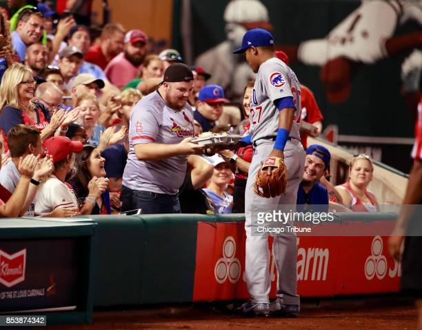 Chicago Cubs shortstop Addison Russell replaces a fan's nachos who lost them when Russell went into the stands after a ball during the second inning...