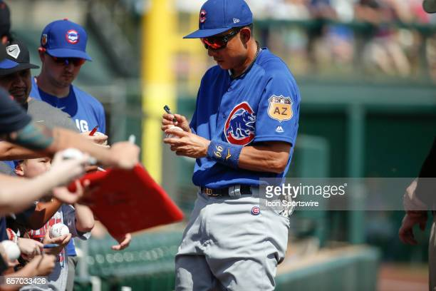 Chicago Cubs shortstop Munenori Kawasaki autographs a baseball before the spring training baseball game between the Chicago Cubs and the Colorado...
