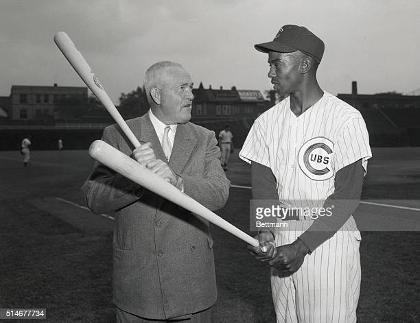 Chicago Cubs star shortstop Ernie Banks receives batting advice from Rogers Hornsby one of baseball's great hitting stars and current batting coach...