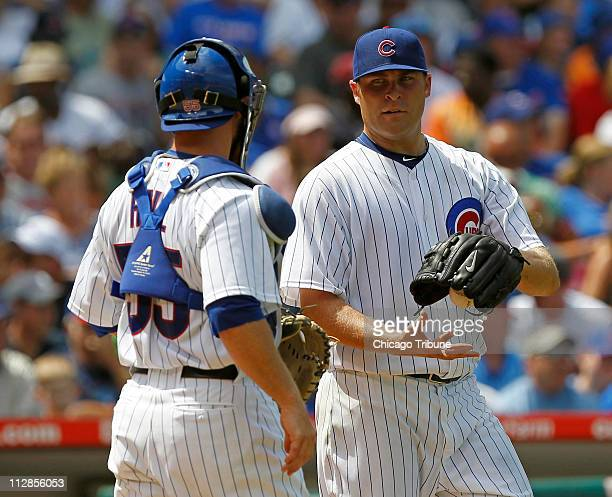 Chicago Cubs starting pitcher Thomas Diamond talks with catcher Koyie Hill after a sacrifice fly by Cincinnati Reds Ryan Hanigan scores a run in the...