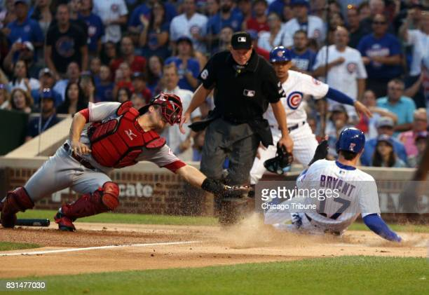 Chicago Cubs third baseman Kris Bryant scores past Cincinnati Reds catcher Devin Mesoraco on the double by Chicago Cubs first baseman Anthony Rizzo...