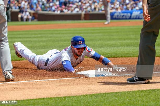 Chicago Cubs third baseman Kris Bryant slides safety to third base after Chicago Cubs left fielder Kyle Schwarber hit a flyout during the first...