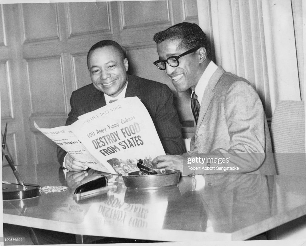 Chicago Daily Defender publisher and Sengstacke Newspapers Board Chair John H. Sengstacke (1912 � 1997) examining a copy of the Daily Defender with entertainer Sammy Davis, Jr. (1925 � 1990), Chicago, ca.1956. The Defender became a daily publication in 1956.