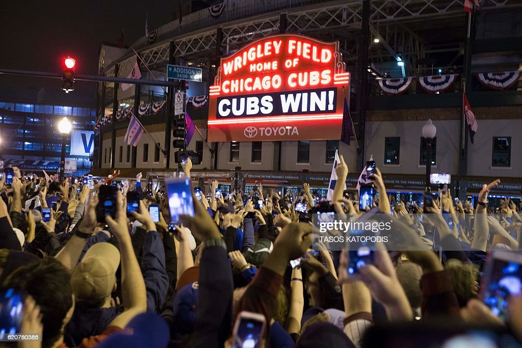 Chicago fans celebrate the Chicago Cubs 8-7 victory over the Cleveland Indians in Cleveland in 10th inning in game seven of the 2016 World Series, outside Wrigley Field in Chicago, Illinois early on November 3, 2016. Ending America's longest sports title drought in dramatic fashion, the Chicago Cubs captured their first World Series since 1908 by defeating the Cleveland Indians 8-7 in a 10-inning thriller that concluded early on November 3. / AFP / Tasos Katopodis
