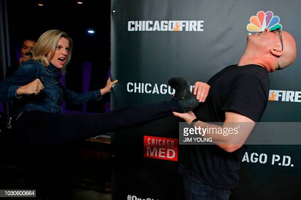Chicago Fire cast member Kara Killmer jokingly kicks executive producer Derek Haas as they arrive on the red carpet for the 4th Annual OneChicago...