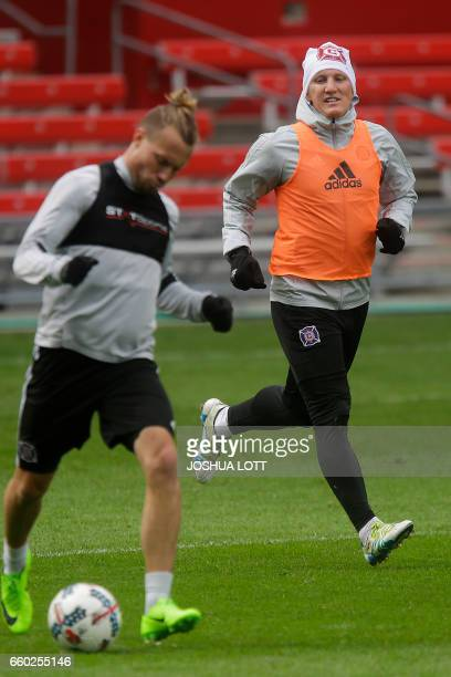 Chicago Fire German midfielder Bastian Schweinsteiger watches as defender Michael Harrington controls the ball during a team scrimmage at Toyota Park...