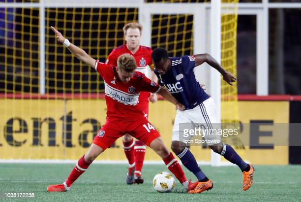 Chicago Fire midfielder Djordje Mihailovic holds off New England Revolution forward Cristian Penilla during a match between the New England...