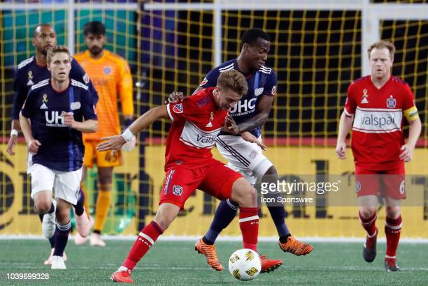 Chicago Fire midfielder Djordje Mihailovic keeps the ball from New England Revolution forward Cristian Penilla during a match between the New England...