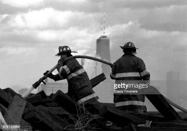 Chicago firefighters extinguish a rubbish fire on Goose Island with the Hancock Building in the background in Chicago Illinois USA in 1993