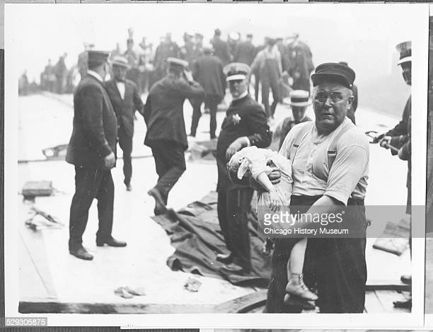 Chicago fireman Leonard E. Olson carrying a child from the Eastland Disaster, Chicago, Illinois, 1915. He received the Lambert Tree Medal for his...